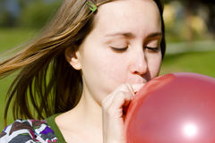 Young woman inflating red balloon. In the park Stock Image