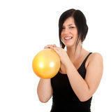 Young woman inflating yellow balloon Stock Images