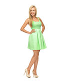 Young woman ingreen dress and high heels. Beauty, fashion and happy people concept - young woman in green dress and high heels Stock Images