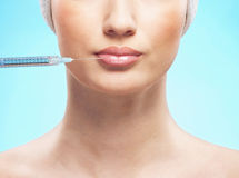 A young woman injecting botox into her lower lip Stock Image