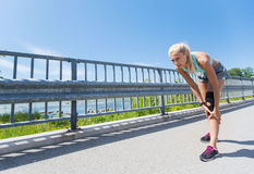 Young woman with injured knee or leg outdoors Stock Photography