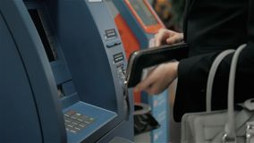 Young woman inserting a credit card to ATM, beautiful girl banking, business woman after work in bank, shopping mall. Young woman inserting a credit card to ATM stock footage