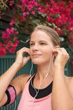 Young woman inserting ear phones in her ears stock photos