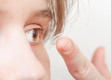 Young woman inserts corrective lens in eye Royalty Free Stock Photos