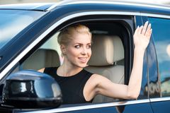Young woman inside car waving Royalty Free Stock Photo