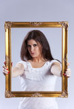 Young woman inside a picture frame Royalty Free Stock Image