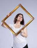 Young woman inside a picture frame Stock Photography