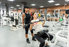 Young woman with an instructor in the gym Royalty Free Stock Photo