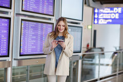 Young woman at international airport, checking electronic board Royalty Free Stock Photos