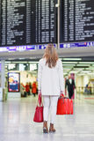 Young woman at international airport, checking electronic board Royalty Free Stock Image