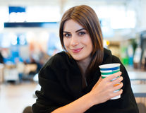 Young woman at international airport, drinking coffee Stock Photo