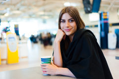 Young woman at international airport, drinking coffee Stock Images