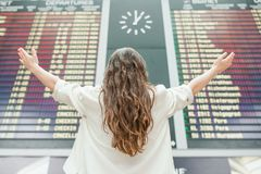 Young woman in international airport looking at the flight information board checking for flight Stock Images