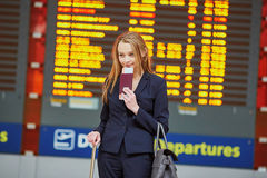 Young woman in international airport looking at the flight information board, checking her flight Stock Images