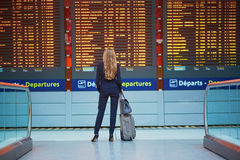 Young woman in international airport looking at the flight information board, checking her flight Stock Photography