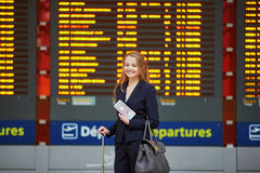 Young woman in international airport looking at the flight information board, checking her flight Stock Photos