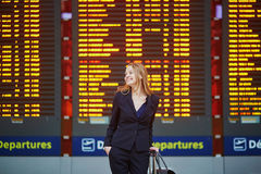 Young woman in international airport looking at the flight information board, checking her flight Royalty Free Stock Images