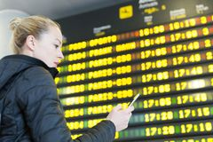 Woman at airport in front of flight information board checking her phone. Young woman at international airport looking at the flight information board, holding Stock Photography