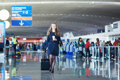 Young woman in international airport. Walking with her luggage with coffee to go Stock Image