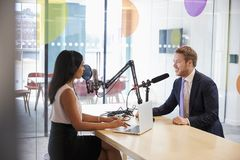 Young woman interviewing a guest in a studio for a podcast royalty free stock photography