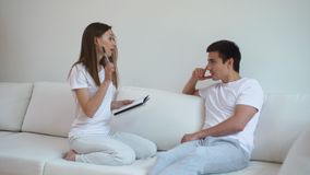 Young woman interviews man in friendly atmosphere. Girl and guy communication. Young woman interviews man in friendly atmosphere. Girl and guy smile in process stock footage