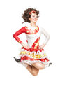 Young woman in irish dance dress dancing isolated. Young woman in irish dance dress and wig dancing isolated Stock Photos