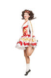 Young woman in irish dance dress dancing isolated. Young woman in irish dance dress and wig dancing isolated Stock Image