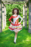 Young woman in irish dance dress dancing outdoor. Young woman in irish dance dress and wig dancing outdoor Royalty Free Stock Photo