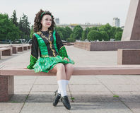 Young woman in irish dance dress sitting on the bench Royalty Free Stock Images