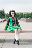 Young woman in irish dance dress sitting on the bench Royalty Free Stock Photo