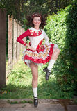 Young woman in irish dance dress and wig dancing. Outdoor Royalty Free Stock Photo