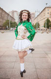 Young woman in irish dance dress and wig dancing Stock Photos