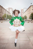 Young woman in irish dance dress and wig dancing Stock Photography
