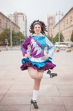 Young woman in irish dance dress and wig dancing. Outdoor Stock Photo