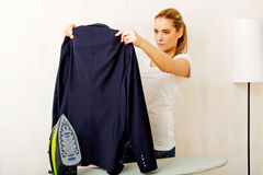 Young woman ironig man's jacket on ironing board Royalty Free Stock Photos