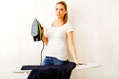 Young woman ironig man's jacket on ironing board Stock Photo