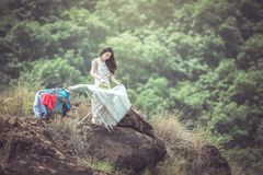 Young women ironing on cliffs in nature, working life concept of royalty free stock image