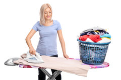 Young woman ironing clothes. Young blond woman ironing clothes on an ironing board isolated on white background stock photography