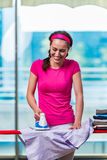 The young woman ironing clothing on board Royalty Free Stock Photo