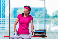 The young woman ironing clothing on board Stock Photos