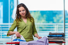 The young woman ironing clothing on board Stock Image