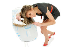 Young woman ironing curly hair Stock Photos
