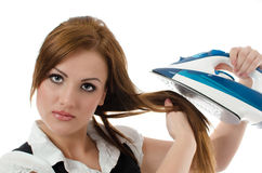 Young woman ironing her hair Stock Images