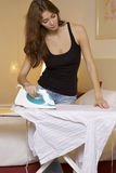 Young woman ironing on ironing board Royalty Free Stock Photography