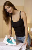 Young woman ironing on ironing board Royalty Free Stock Photos