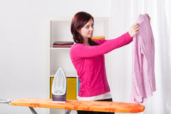 Young woman ironing shirt Stock Image