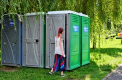 Free Young Woman Is Entering A Portable Toilet Royalty Free Stock Photo - 180679345