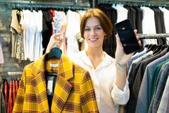 Young Woman Is Holding Black Cellphone And Checkered Coat Of Yellow Color In Clothing Shop For Women Royalty Free Stock Photography