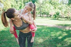 Free Young Woman Is Standing Outside In Park And Holding Her Daughter On Her Back. She Is Holding Her On Her Legs And Looking Royalty Free Stock Image - 117318036