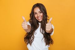 Young woman isolated over yellow background showing thumbs up gesture. Image of happy young woman isolated over yellow background showing thumbs up gesture stock photos